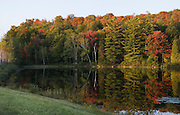 Adirondack trees in fall colors reflect in a small lake.