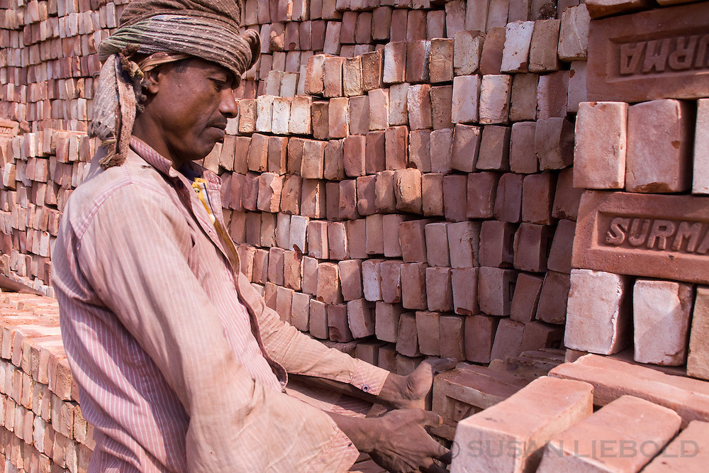 A man stacking bricks after they've been fired in the kiln, Bangladesh.