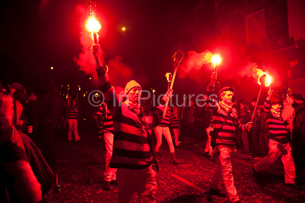Lewes, UK. Monday 5th November 2012. Southover bonfire society members carry burning torches. Bonfire Night celebration in the town of Lewes, East Sussex, UK which form the largest and most famous Guy Fawkes Night festivities. Held on 5 November, the event not only marks the date of the uncovering of the Gunpowder Treason and Plot in 1605, but also commemorates the memory of the 17 Protestant martyrs from the town burnt at the stake for their faith during the Marian Persecutions of 1555–57. There are six bonfire societies putting on parades involving some 3,000 people.
