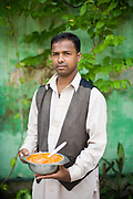 A waiter holds a bowl of butter chicken at Moti Mahal Restaurant in Old Delhi, India<br /> The Moti Mahal restaurant, a Delhi landmark, opened in 1947 is widely credited with inventing the classic Delhi dish, butter chicken