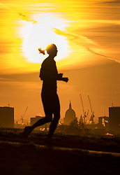 © Licensed to London News Pictures. 30/01/2018. London, UK. A jogger enjoys the sunrise over central London from the top of a frosty Primrose Hill. Photo credit: Peter Macdiarmid/LNP