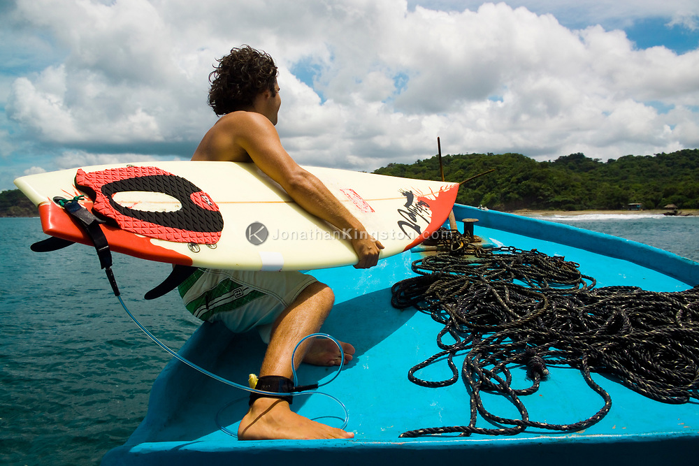 A surfer prepares to jump off the boat to catch a wave in to Maderas Beach, located near San Juan Del Sur, Nicaragua. Once a little known and sleepy vacation spot, San Juan Del Sur has become increasingly popular for its beautiful beaches, small fishing town feel, and respected surf break.