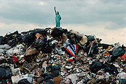 Garbage barges transported some 20,000 tons of garbage out of New York City to Fresh Kills landfill in Staten Island every day for several decades.  For a story I proposed on trash to National Geographic, I decided to ride a garbage barge as it motored past Gotham. Getting the pile of trash with the city in the background would be a powerful juxtaposition.  Having finished the shoot and waiting to get out of the stinking barge to the dump, I began strolling down the rows of barges back to the pilot house when I noticed the plastic American flag banner just as we were drifting by the Statue of Liberty.   I quickly climbed onto the revolting refuse and snapped about 10 pictures before we sailed out of range. Inspecting the film, I later noticed that there were quite a few other objects in the trash with the banner, including the infamous, kitchen sink.  After this shot was taken, barges had to be covered with giant nets so trash wouldn't blow into the rivers and bay.  Freshkills Landfull was declared full in 2001 and later reopened in 2002 to discard the Trade Towers.