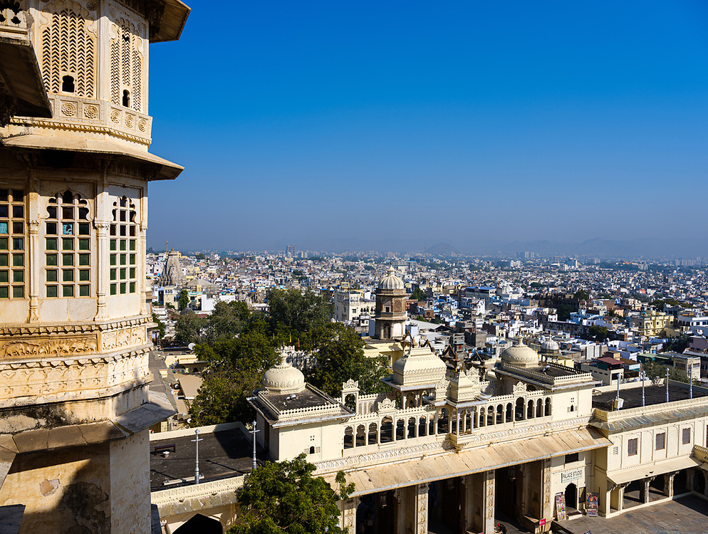 """UDAIPUR, INDIA - CIRCA NOVEMBER 2018: Panoramic view of Udaipur from the City Palace. The city is the historic capital of the kingdom of Mewar. Surrounded by Aravali Range, which separates it from Thar Desert, and full of lakes Udapiur is also known as the """"City of Lakes"""" and dubbed as the most romantic spot of the Indian Continent."""