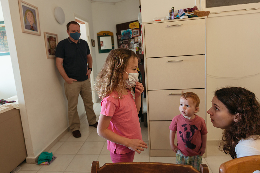 Clil Michel adjusts a protective face mask as her brother Ofek, and her parents Anna and Matti watch, while she prepares for school, at her home in Jerusalem, Israel, on May 3, 2020.
