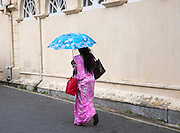 Woman walking with umbrella for shade by the fort walls in the historic town of Galle, Sri Lanka, Asia