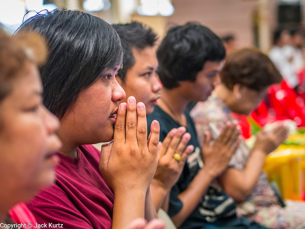 """12 OCTOBER 2012 - RAI KHRING, NAKHON PATHOM, THAILAND:   Thais pray during a Buddhist chanting and merit making service at Wat Rai Khring in Nakhon Pathom province. Wat Rai Khring was built in 1791, the Abbot at the time, Somdej Phra Phuttha Chan (Pook), named this temple after the district. When construction was completed, the Buddha image was brought from another temple and enshrined here. Later locals named the image """"Luang Pho Wat Rai Khing"""". The Buddha image is of Chiang Saen style and is assumed to have been built by Lanna Thai and Lan Chang craftsmen.    PHOTO BY JACK KURTZ"""