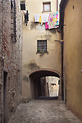 A person hangs colorful laundry over a narrow medieval street in San Gigmangno, Tuscany, Italy