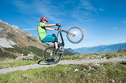 Mountain biker riding on back wheel through mountain, Tirol, Austria