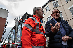 """© Licensed to London News Pictures. 16/11/2019. Bolton, UK. Assistant County Fire Officer DAVE KEELAN and President and Vice Chancellor of the University of Bolton PROFESSOR GEORGE HOLMES at a press conference at the scene as firefighters work after a fire broke out overnight (15th/16th November 2019) at a block of flats known as """" The Cube """" , in Bolton Town Centre . At least two people are known to have been treated by paramedics at the scene of the six-story block , which is occupied by students of the University of Bolton . Photo credit: Joel Goodman/LNP"""