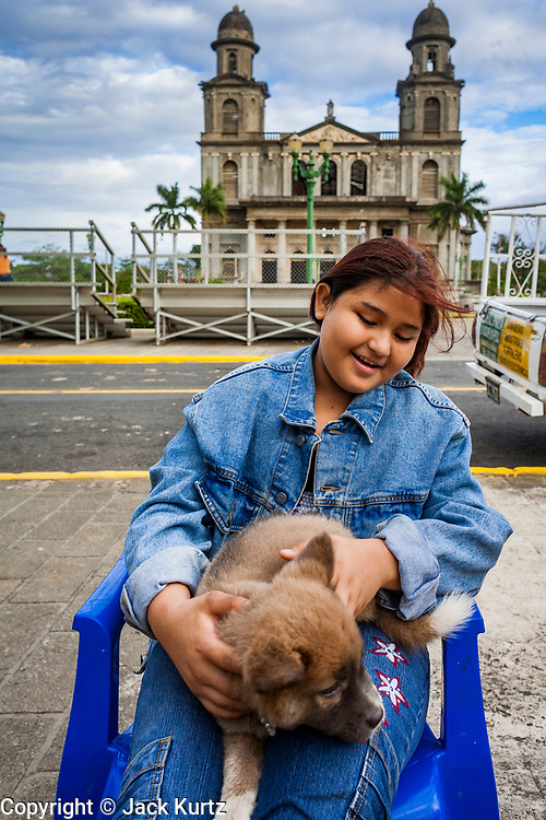 07 JANUARY 2007 - MANAGUA, NICARAGUA: A woman plays with her puppy in front of the historic cathedral in Managua, Nicaragua. The cathedral was destroyed in the 1972 earthquake that destroyed much of the Nicaraguan capitol. The earthquake, and the Somoza regime response to it, was one of the sparks that lead to widespread public support for the Sandanista movement.   Photo by Jack Kurtz