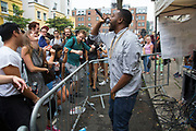 Rapper Tony Wilson at I Spy The People sound system on Colville Gardens. Notting Hill Carnival in West London. A celebration of West Indian / Caribbean culture and Europe's largest street party, festival and parade. Revellers come in their hundreds of thousands to have fun, dance, drink and let go in the brilliant atmosphere. It is led by members of the West Indian / Caribbrean community, particularly the Trinidadian and Tobagonian British population, many of whom have lived in the area since the 1950s. The carnival has attracted up to 2 million people in the past and centres around a parade of floats, dancers and sound systems.