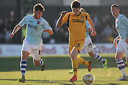 Ryan Burge of Newport runs with the ball under the watch of Jordan Moore-Taylor of Exeter. Skybet football league two match, Newport county v Exeter city at Rodney Parade in Newport, South Wales on Sunday 16th March 2014.<br /> pic by Mark Hawkins, Andrew Orchard sports photography.