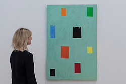 "© Licensed to London News Pictures. 07/06/2016. London, UK.   A staff member views ""311 Castro Street"", by the American artist Mary Heilmann, which is previewed ahead of her first major UK exhibition, ""Looking at Pictures"", at the Whitechapel Gallery.  The exhibition spans the artist's five decade career, from her early geometric paintings made in the 1970s to her recent shaped canvases in day-glo colours.  The show features approximately 45 paintings as well as a selection of ceramics, chairs and works on paper, many of which have never been exhibited.  Photo credit : Stephen Chung/LNP"