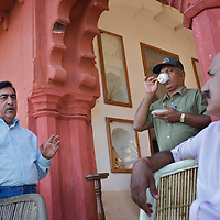 At the senior government guesthouse of Jogi Mahal a day before the planned relocation of a tiger from Rantambore to Sariska, R.N. Mehrotra (left), Chief Wildlife officer for Rajasthan, discusses strategy with Rajpal Singh, Member of the Rajasthan Tiger Task Force (right) and Divisional Forest officer R.S. Shekhawat (drinking tea)...Sariska National Park in Rajasthan was once home to dozens of tigers but by 2005 poaching had resulted in their complete eradication. Recognising the urgent need for intervention, the Indian and Rajasthan-state governments began the reintroduction of tigers into Sariska. Two cats were airlifted 200 km from Ranthambore National Park in June 2008. On November 5th an attempt to relocate a third tiger was postponed until later in the month. This relocation strategy is certainly an important part of the tiger conservation effort but many, including those like Dharmendra Khandal of the NGO Tiger Watch, argue that it will never be entirely successful without properly confronting the three essential issues that threaten tiger populations: poaching, habitat loss and the hunting of prey-base animals. In turn, these three issues cannot be addressed without acknowledging the malign influence of caste, poverty and poor administrative accountability. Poaching is almost exclusively undertaken by extremely poor and marginalised groups, including the Mogia caste who, without education, land and access to credit have limited alternative means of income. Many in the Mogia community also hunt bush meat for both their own consumption and to sell to others. This results in a depletion of the prey-base upon which tigers feed. Encroachment and grazing by those including the Gujar people who raise dairy herds, have led to habitat loss in Sariska and other parks. To properly tackle the problem of hunting and encroachment, the government must provide alternative livelihoods for marginalised groups and relocate them to viable land before - rather than after - the re