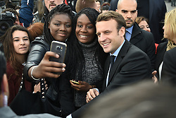 Presidential election candidate for the En Marche ! movement Emmanuel Macron poses for a selfie with supporters outside the Amiens Cathedral on April 26, 2017. Macron announced that he would meet with employees of the under-threat Whirlpool factory in Amiens after French far-right presidential candidate Marine Le Pen upstaged him by making a surprise visit to the factory as he was meeting workers' representatives without actually visiting the site. Photo by Eliot Blondet/ABACAPRESS.COM