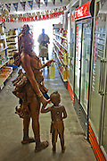 A traditionaly dressed Himba woman shopping with her child in a supermarket in Opuwo, northwestern Namibia. Like most traditional Himba women, she covers herself from head to toe with an ochre powder and cow butter blend..
