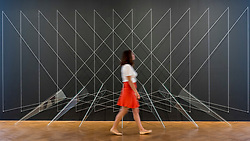 """© Licensed to London News Pictures. 25/06/2018. LONDON, UK. A staff member walks by an artwork by Lydia Okumura. Preview of """"Lands of Lads, Land of Lashes"""", an exhibition of sculptures and paintings by three female artists of the1960s and 1970s - Rosemarie Castoro, Wanda Czelkowska and Lydia Okumura - specialising in Minimal and Post-Minimal art.  The exhibition, held at Galerie Thaddaeus Ropac in Mayfair, runs 25 June to 11 August 2018.  Photo credit: Stephen Chung/LNP"""