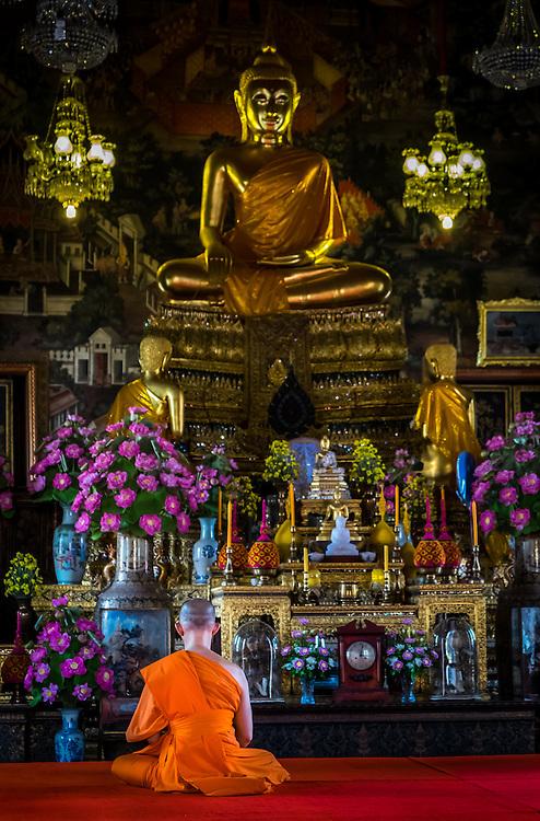 BANGKOK, THAILAND - CIRCA SEPTEMBER 2014: Buddhist monk praying inside the Ordination Hall in  Wat Arun, a  popular Buddhist temple in Bangkok Yai district of Bangkok, Thailand, on the Thonburi west bank of the Chao Phraya River