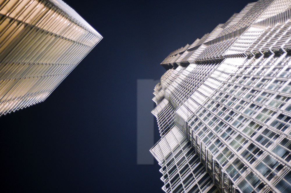 At night, two skyscrapers raise to a dark sky. Architecture's buliding is very geometric and brings the feeling of being in a science fiction scene. Shanghai, China, Asia.