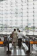 Berlin, Germany - September 3, 2015: Two women use an escalator to move toward the exit at the Berlin Hauptbahnhof, the main train station in Berlin, Germany. The station was designed by the architect Meinhard von Gerkan of Gerkan, Marg and Partners.