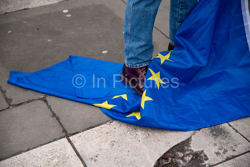 A leave supporter stands on a EU flag in Parliament Square, London, United Kingdom on 31st January, 2020. The United Kingdom formally leaves the European Union at 23:00 GMT today.