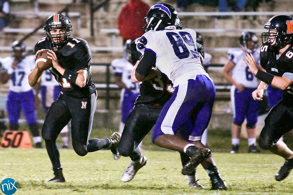 Trojans quarterback Damian Bertino (11, left) rolls out behind a block during the Cox Mill Chargers at Northwest Cabarrus Trojans high school football game on Friday night.