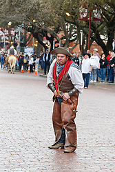 Cowboy on street helping drovers on horseback move Texas longhorns on East Exchange  Ave. during daily Fort Worth Herd Cattle Drive, Fort Worth Herd  Fort Worth Stockyards National Historic District, Fort Worth, Texas, USA.