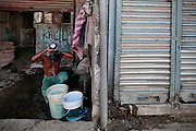 A man bathes outside his home using water he collected with buckets from one of the few water sources in the slum.  The slum of Cheetah Camp on the outskirts of Mumbai, India is a predominantly muslim community on living on the fringe while the city continues to grow.