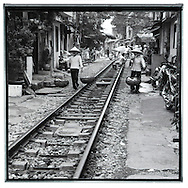Two vietnamese women walk along the railway of Hanoi. They carry their yoke. In this place, houses and buildings are constructed along the railway. they were the traditional conic hat.