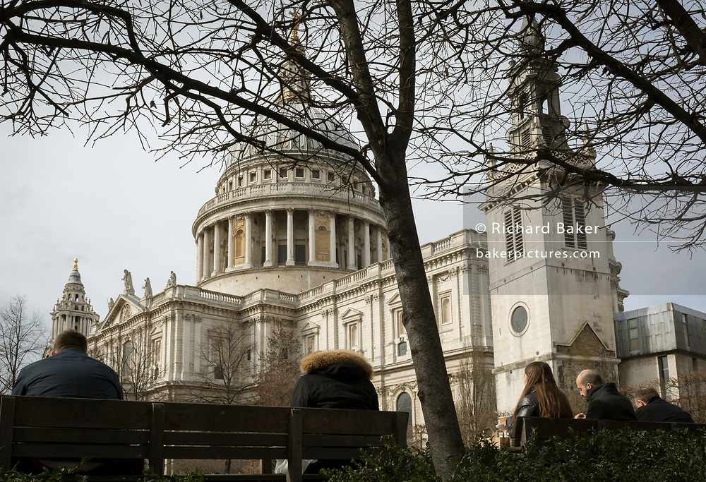 Londoners rest on benches beneath St Paul's Cathedral in the City of London, the capital's financial district, on 14th March 2018, in London England.