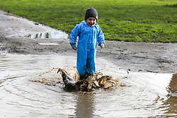 © Licensed to London News Pictures. 05/02/2021. London, UK. Presiyan age 2  plays in a large puddle of water in Chestnuts Park, north London. Part of the footpath in the park is flooded following heavy overnight rain in London. According to the Met Office, snow is forecast for the weekend. <br /> <br /> ***Permission Granted***<br /> <br />  Photo credit: Dinendra Haria/LNP