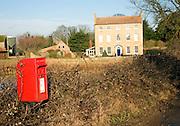 Red post box and Georgian farmhouse, Bawdsey, Suffolk, England