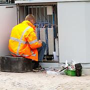 NLD/Amsterdam/20150620 - Monteur tijdens de weekenddienst aan het werk in een telefoonkast in Amsterdam