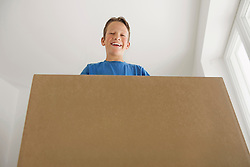 Young boy carrying big cardboard box new home
