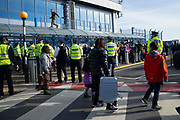 Passengers look on as a climate change protester from group Extinction Rebellion runs along a roof at London City Airport during day four of two weeks of planned demonstrations on 10th October, 2019 in London, Untited Kingdom. Extinction Rebellion is demanding that governments drastically cut carbon emissions.