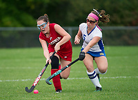 Laconia's Katie DiBona and Gilford's Kellie Ryan charge the ball during NHIAA Division III field hockey on Wednesday.  (Karen Bobotas/for the Laconia Daily Sun)