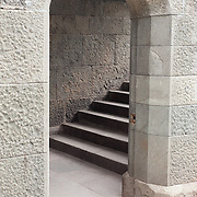 An old doorway in a stone wall, with a staircase.