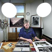 Nederland, Amsterdam , 1 november 2010..Fotograaf Paul Fennes in zijn woonkamer met oude stadsprenten. Paul Fennes heeft onlangs het boek samengesteld getiteld de buurten van Oud West..Foto:Jean-Pierre Jans