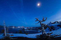 The moon rises over snowy Crater Lake, Oregon on a winter night.