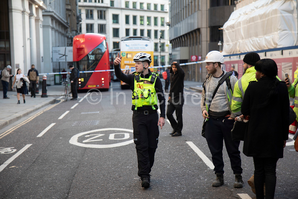 Police ask the public to move away from the scene as the City of London is locked down by Metropolitan and City Police following what is believed to have been a terror-related incident on London Bridge at around 2pm on 29th November 2019 in London, United Kingdom. Police officers cordoned off the bridge, underpass and all surrounding roads following the incident during which members of the public intervened before shots were fired by armed police. The incident is said to have started as a stabbing during which a number of people were stabbed in a building near London Bridge.