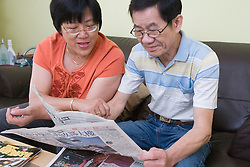Couple reading Chinese newspaper together,