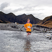 Runner Matthew McLean crosses Moke Creek on the Ben Lomond High Country Station during the Pure South Shotover Moonlight Mountain Marathon and trail runs. Moke Lake, Queenstown, New Zealand. 4th February 2012. Photo Tim Clayton