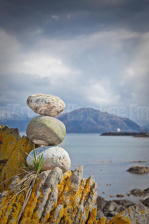 En liten mini varde står og speider ut mot havet. Fyren i bakgrunnen.