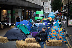 © Licensed to London News Pictures. 31/08/2019. Manchester, UK. Extinction Rebellion block roads around Deansgate in Manchester City Centre and pitch tents , during days of planned disruption organised by environmental campaigners . Manchester City Council has declared a climate emergency but activists say the council's development plans do not reflect this . Photo credit: Joel Goodman/LNP