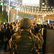 Charlotte, NC- September 23, 2016:  A National Guard waves to demonstrators as they pass by along 7th Street in uptown Charlotte.  CREDIT: LOGAN R. CYRUS FOR THE NEW YORK TIMES