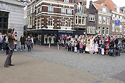 Een fotograaf maakt een groepsfoto van een bruidspaar met gezelschap in het centrum van Utrecht.<br /> <br /> A photographer is making a group portrait during a wedding at the center of Utrecht.
