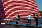 Artist Christo walks out onto a pontoon to view his art installation The Mastaba, by artist Christo, installed on the Serpentine lake in Hyde Park on June 18th 2018 in London, United Kingdom. The sculpture consists of 7,506 stacked barrels, painted in shades of red, white, blue and mauve. The completed piece forms part of an exhibition by Christo and his late wife, Jeanne-Claudes work, entitled Christo and Jeanne-Claude: Barrels and The Mastaba 19582018 to be held at The Serpentine Gallery.