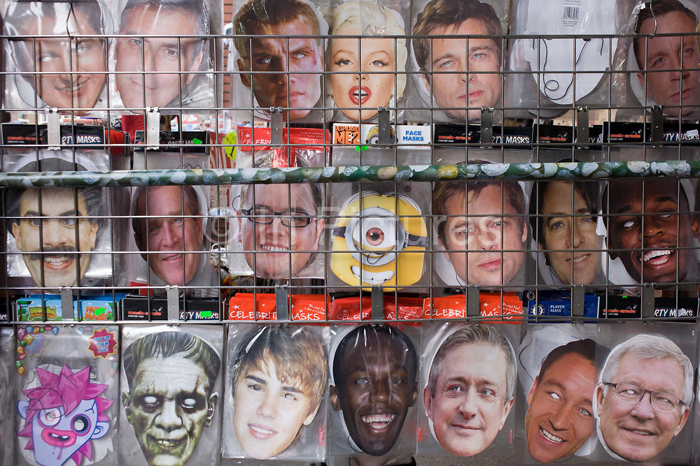 Detail of celebrity faces masks lined-up in a west end tourist shop rack. Actors such as George Clooney, Marylin Monroe, Daniel Craig and Brad Pitt; politician George W Bush and football manager Sir Alex Ferguson are seen behind the wire cage of this tourism retailer in central London. Seen in the rows and columns is a scene of fame and stardom: The popular personalities of showbiz, politics and sport, on sale for an insatiable wannabe audience.
