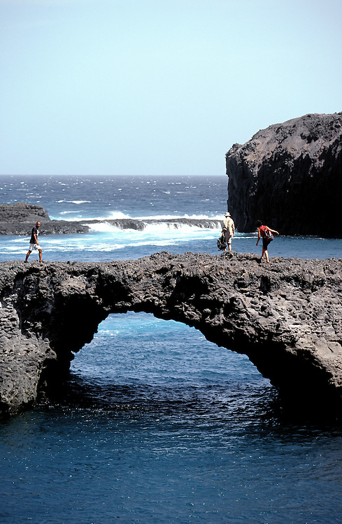 Tourists walk on the borders of Salina's natural pool. The pool was formed by ancient lava rock that reached the sea during Fogo's volcano eruptions.